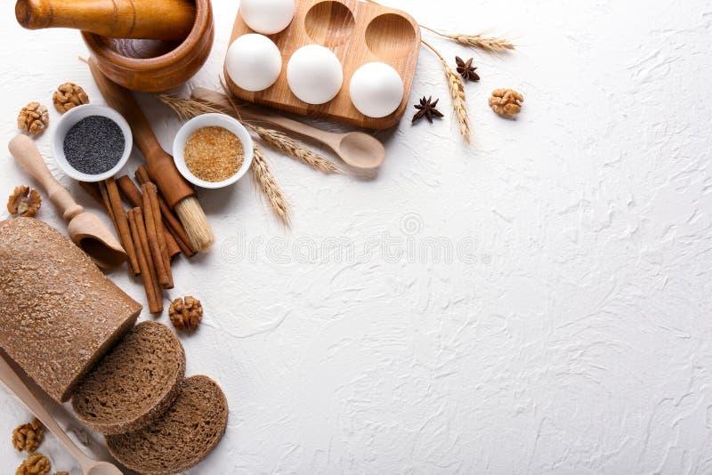 Σύνθεση με το μαγείρεμα των εργαλείων και των συστατικών για την προετοιμασία των ζυμών και του φρέσκου ψωμιού στο άσπρο κατασκευ στοκ φωτογραφίες με δικαίωμα ελεύθερης χρήσης