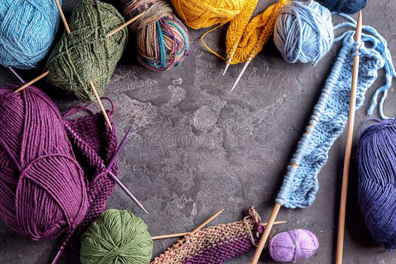 Σύνθεση με το πλέκοντας νήμα και τις βελόνες στο γκρίζο κατασκευασμένο υπόβαθρο στοκ φωτογραφίες