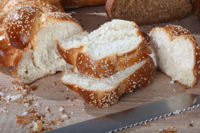 Σύνθεση με το τεμαχισμένο ψάθινο ψωμί με μια κινηματογράφηση σε πρώτο πλάνο μαχαιριών στοκ εικόνες