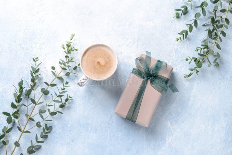 Σύνθεση με το φλιτζάνι του καφέ, το κιβώτιο δώρων και τους κλάδους ευκαλύπτων στο υπόβαθρο χρώματος στοκ εικόνα