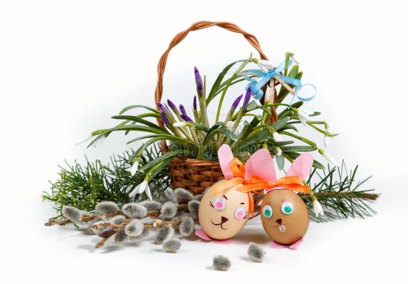 Σύνθεση Πάσχας άνοιξη, διακοσμητικά κουνέλια - τα αυγά, στο καλάθι υποβάθρου με την άνοιξη ανθίζουν στοκ εικόνα