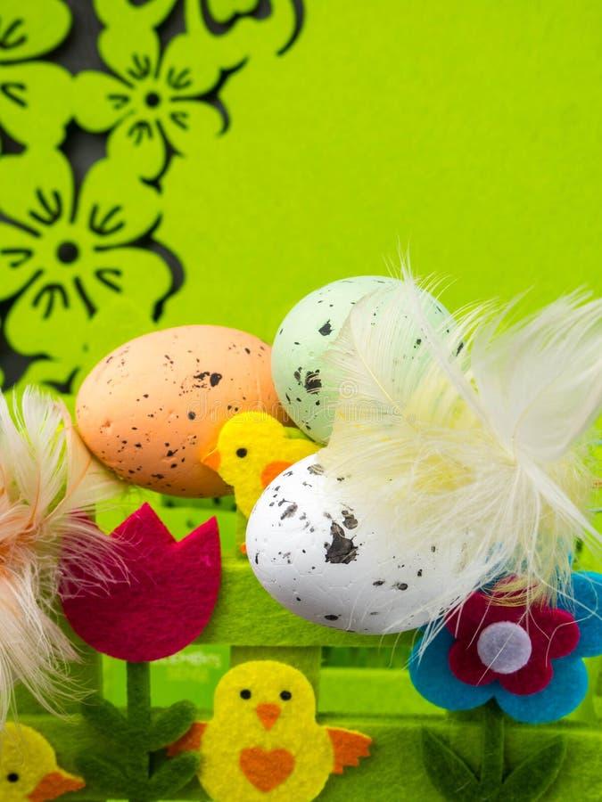 Σύνθεση Πάσχας, ζωηρόχρωμα αυγά με τα φτερά, τα διακοσμητικά λουλούδια και τον κίτρινο νεοσσό στοκ φωτογραφία
