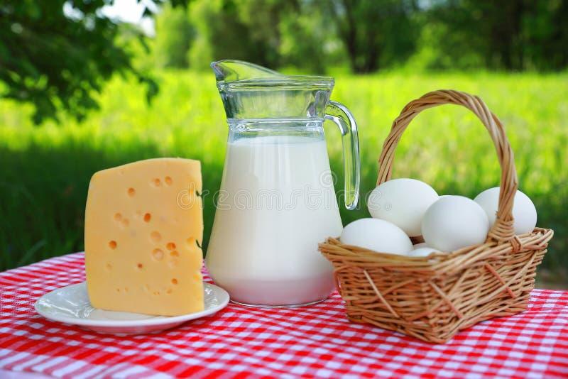 Σύνθεση προγευμάτων μιας κανάτας γάλακτος, ενός καλαθιού των αυγών και ενός κομματιού του τυριού σε ένα πιάτο σε ένα κόκκινος-και στοκ εικόνες