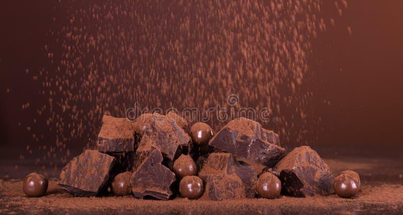 Σύνθεση σοκολάτας Κομμάτια της αρωματικής σοκολάτας, και μια στρογγυλή καραμέλα στη σκόνη κακάου στο σκοτεινό υπόβαθρο στοκ φωτογραφίες