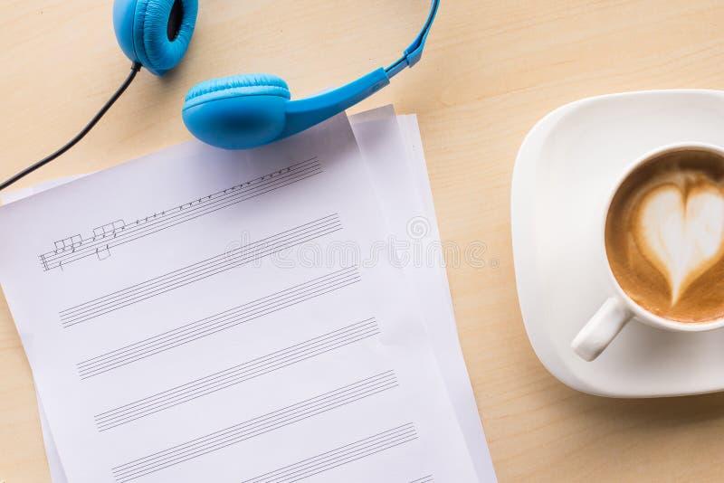 σύνθεση της τοπ άποψης σημειώσεων μουσικής με τον καφέ και το μπλε ακουστικό στοκ φωτογραφία