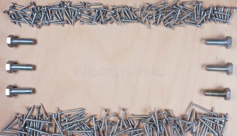 Σύνθεση του πληρώματος και των μπουλονιών στο ξύλινο υπόβαθρο με το διάστημα αντιγράφων για το κείμενό σας στοκ φωτογραφίες