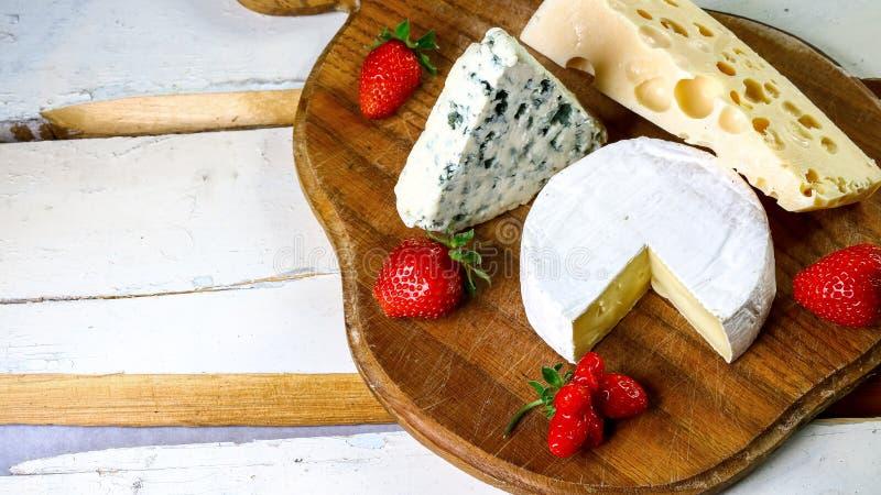 Σύνθεση του τυριού στον ξύλινο πίνακα Camembert, τυρί με το μπλε ωίδιο, γκούντα, σκληρό τυρί, φράουλες, φύλλα μεντών, μαχαίρια στοκ φωτογραφίες