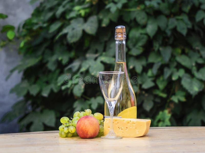 Σύνθεση του τυριού, των σταφυλιών, των ροδάκινων, του κρασιού λευκού, μπουκαλιών και γυαλιών σε μια ξύλινη διάσκεψη στρογγυλής τρ στοκ εικόνες