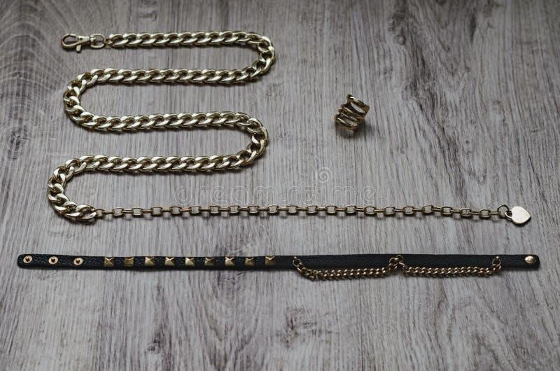 Σύνθεση του bijouterie, της χρυσής αλυσίδας υπό μορφή φιδιού, του χρυσού δαχτυλιδιού και των μαύρων λουριών δέρματος με χρυσό στοκ εικόνες