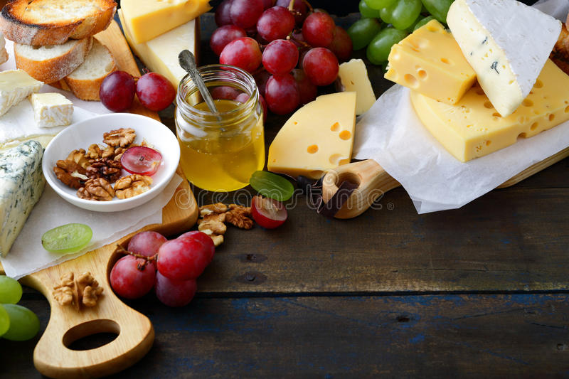 Σύνθεση των διαφορετικών τυριών, των σταφυλιών, του μελιού, του ψωμιού και των ξύλων καρυδιάς τύπων στο παλαιό ξύλινο υπόβαθρο στοκ φωτογραφίες με δικαίωμα ελεύθερης χρήσης