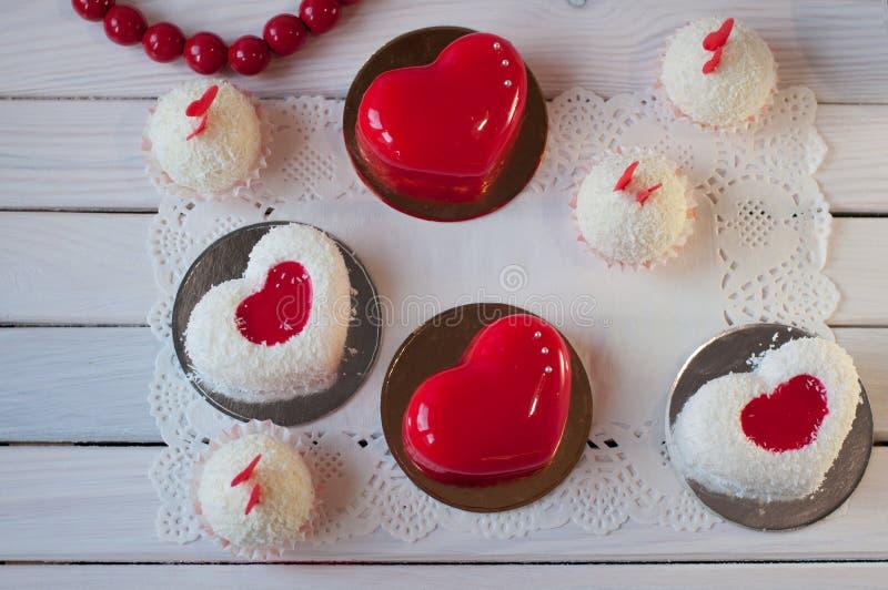 Σύνθεση των κέικ διακοπών Τα κόκκινα, άσπρα κέικ και οι σφαίρες βάζουν στον ξύλινο πίνακα στοκ εικόνα με δικαίωμα ελεύθερης χρήσης