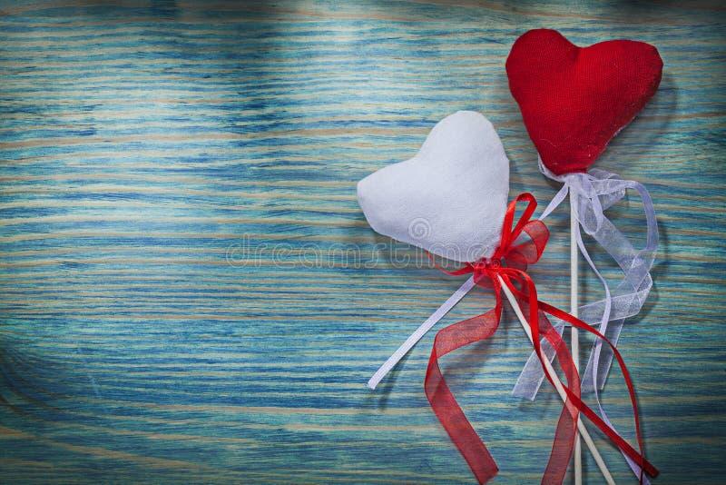 Σύνθεση των κόκκινων και άσπρων καρδιών βαλεντίνων με τις κορδέλλες στο wo στοκ εικόνες