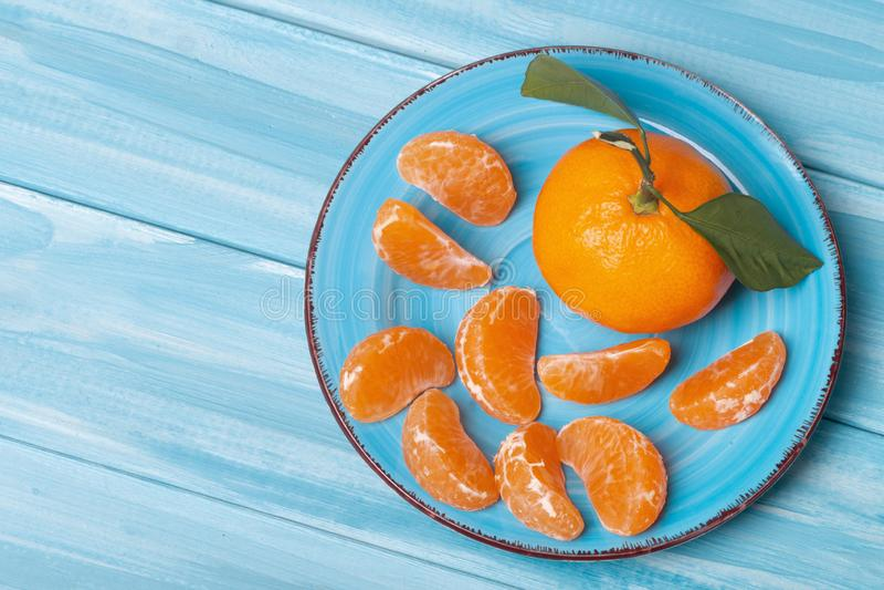 Σύνθεση των tangerines σε μπλε φόντο Κομμάτια φρέσκων, νόστιμων μανταρινιών στο πιάτο στοκ φωτογραφίες