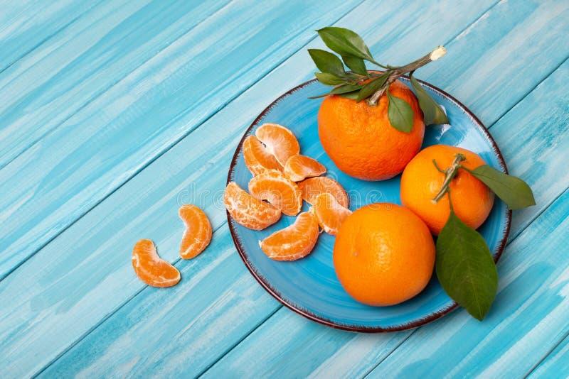 Σύνθεση των tangerines σε μπλε φόντο Κομμάτια φρέσκων, νόστιμων μανταρινιών στο πιάτο στοκ φωτογραφίες με δικαίωμα ελεύθερης χρήσης