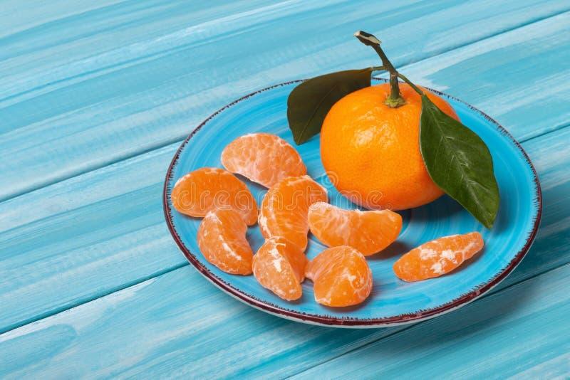 Σύνθεση των tangerines σε μπλε φόντο Κομμάτια φρέσκων, νόστιμων μανταρινιών στο πιάτο στοκ εικόνες