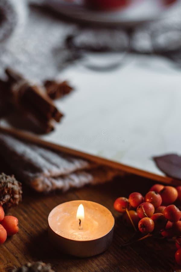 Σύνθεση φθινοπώρου και κεριά και βελόνες στο κατασκευασμένο πουλόβερ στο ξύλινο υπόβαθρο στοκ φωτογραφία