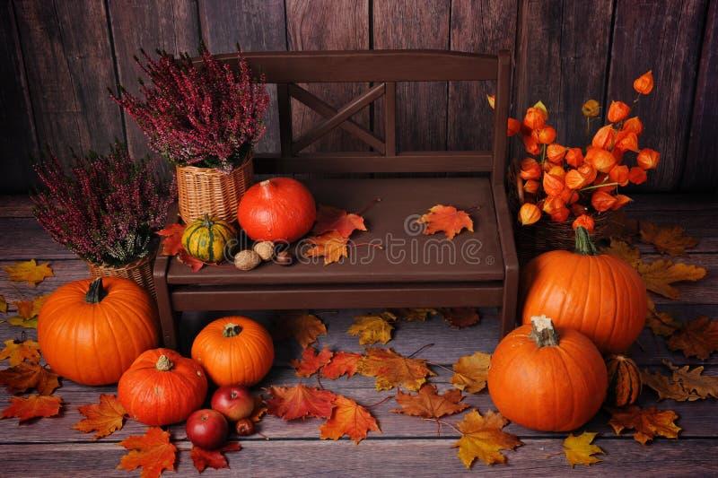 Σύνθεση φθινοπώρου με τις πορτοκαλιές κολοκύθες σε έναν καφετή πάγκο στοκ εικόνες