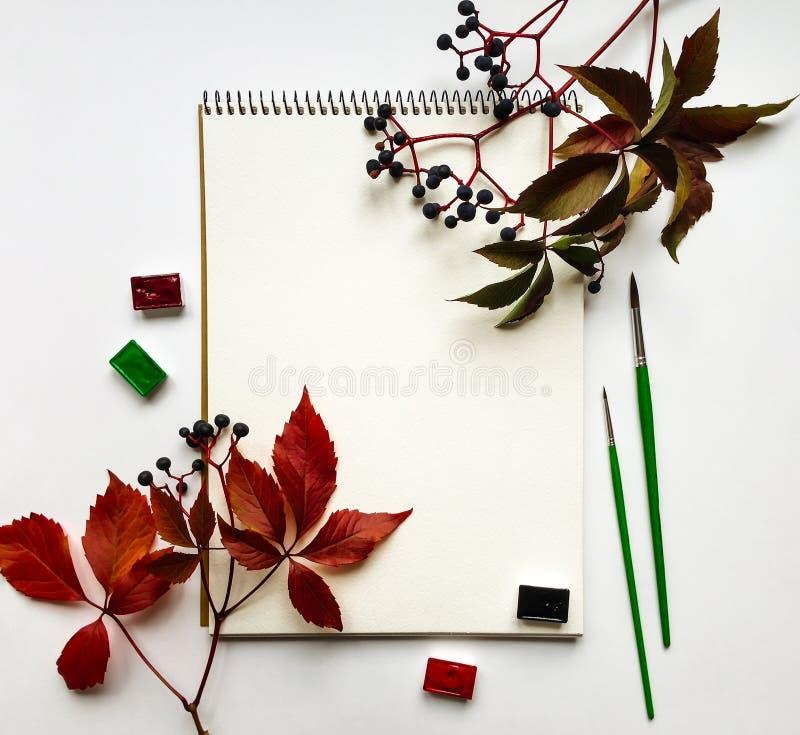 Σύνθεση φθινοπώρου με το λεύκωμα, τα watercolors και τις βούρτσες, που διακοσμούνται με τα κόκκινα φύλλα και τα μούρα Επίπεδος βά στοκ εικόνες