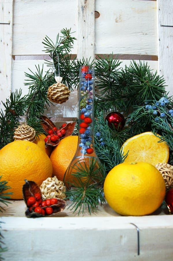 Σύνθεση Χριστουγέννων με ένα μπουκάλι και τα πορτοκάλια στοκ φωτογραφία