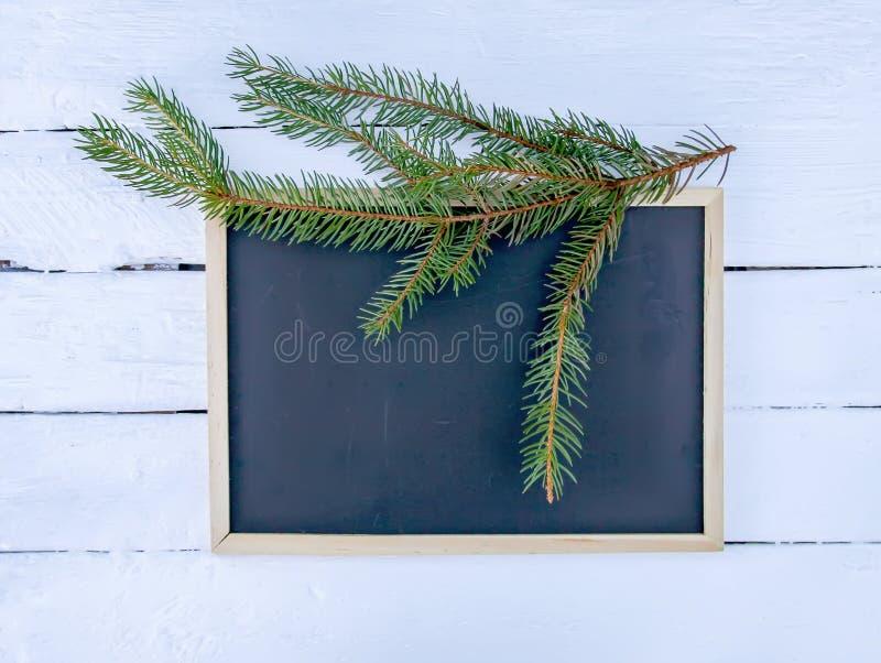Σύνθεση Χριστουγέννων με τον κλάδο έλατου στο άσπρο ηλικίας ξύλινο υπόβαθρο Νέο εορταστικό πρότυπο έτους Κενός πλαισιωμένος πίνακ στοκ φωτογραφίες