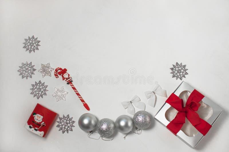Σύνθεση Χριστουγέννων των κόκκινων και ασημένιων διακοσμήσεων, κιβώτιο δώρων με το τόξο κορδελλών, flatlay στοκ εικόνα