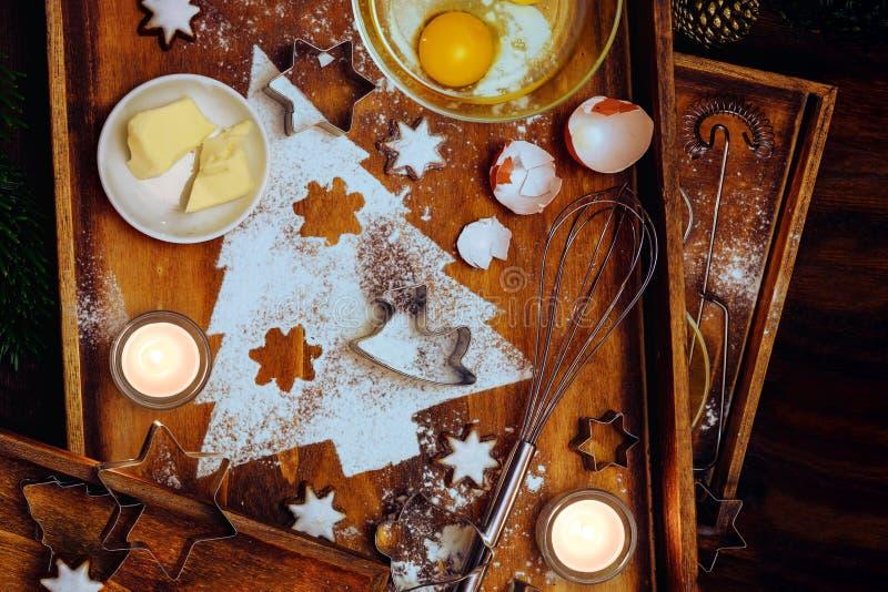 Σύνθεση ψησίματος, σχήμα έλατο από αλεύρι, βούτυρο, αυγό και αστεράκια κανέλας, σκεύη και κεριά σε ζεστό καφέ ξύλινο στοκ εικόνα