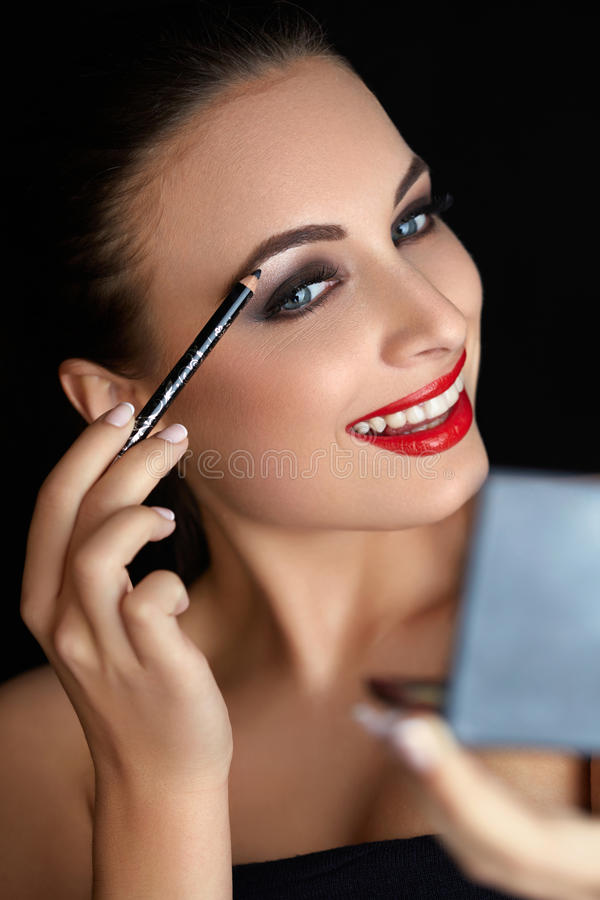 Σύνθεση Όμορφη γυναίκα που κάνει makeup Μολύβι φρυδιών χειλικό κόκκινο στοκ εικόνα με δικαίωμα ελεύθερης χρήσης