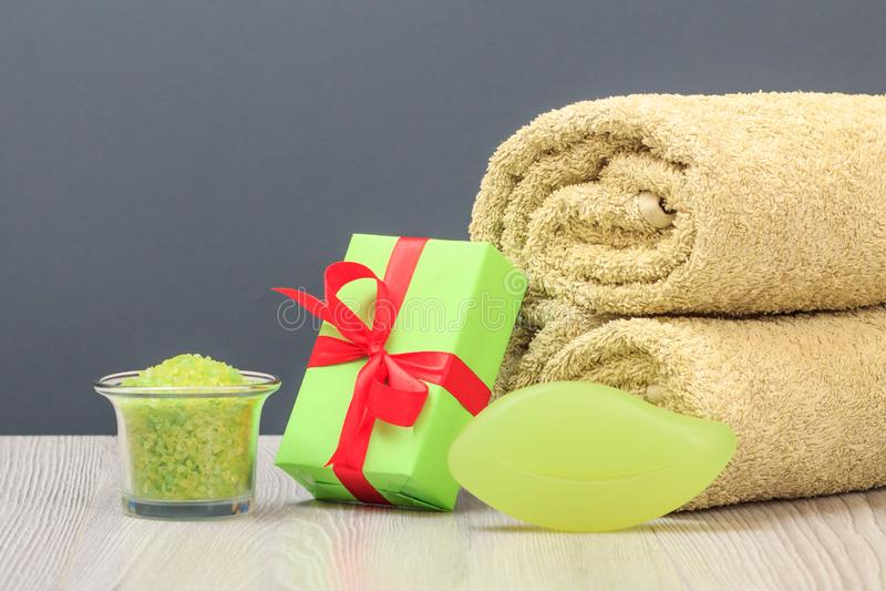 Σύνθεση SPA με τη μαλακή πετσέτα υφασμάτων, το κιβώτιο δώρων, το κύπελλο με το άλας θάλασσας και το σαπούνι στο γκρίζο backgroun στοκ εικόνα με δικαίωμα ελεύθερης χρήσης