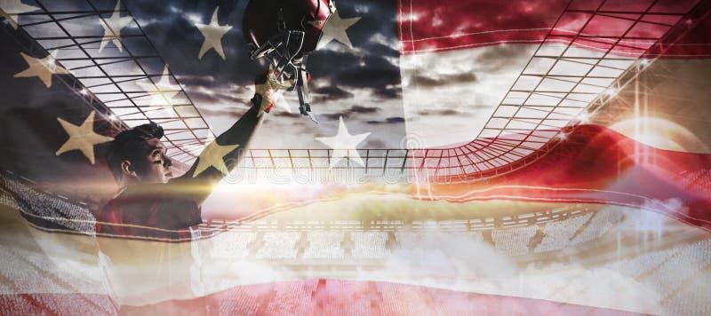 Σύνθετη εικόνα ενθαρρυντικού φορέων αμερικανικού ποδοσφαίρου με το χέρι που αυξάνεται στοκ φωτογραφίες