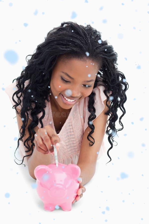 Σύνθετη εικόνα ενός νέου κοριτσιού που βρίσκεται στο πάτωμα που βάζει τα χρήματα σε μια piggy τράπεζα στοκ φωτογραφίες