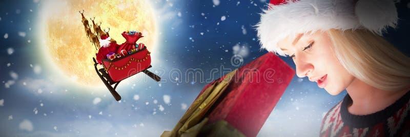 Σύνθετη εικόνα εορταστικού ξανθού ανοίγοντας ένα δώρο στοκ εικόνες