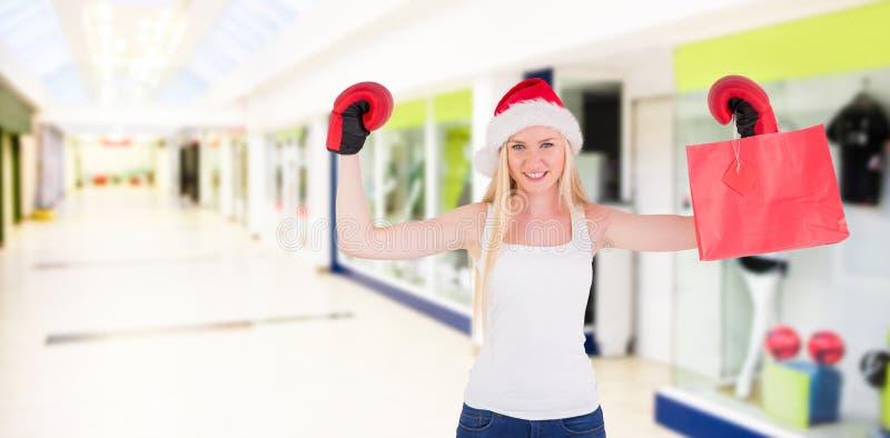 Σύνθετη εικόνα εορταστικού ξανθού ενθαρρυντικού με τα εγκιβωτίζοντας γάντια στοκ εικόνα
