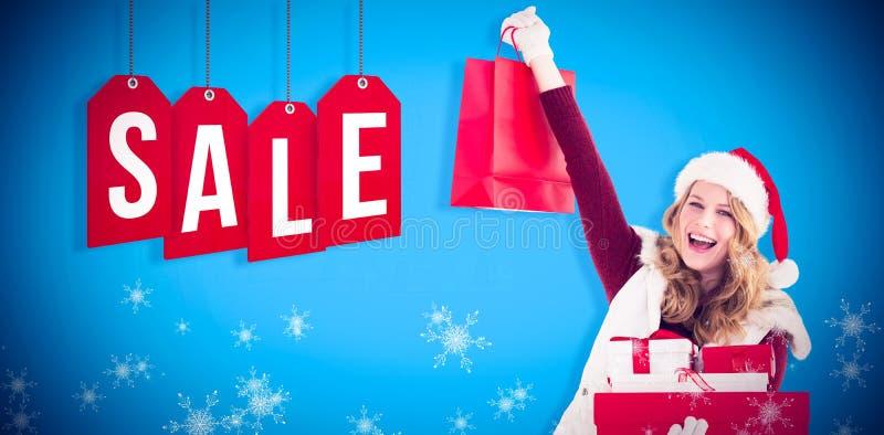 Σύνθετη εικόνα εορταστικού ξανθού με την τσάντα και τα δώρα αγορών στοκ εικόνα με δικαίωμα ελεύθερης χρήσης