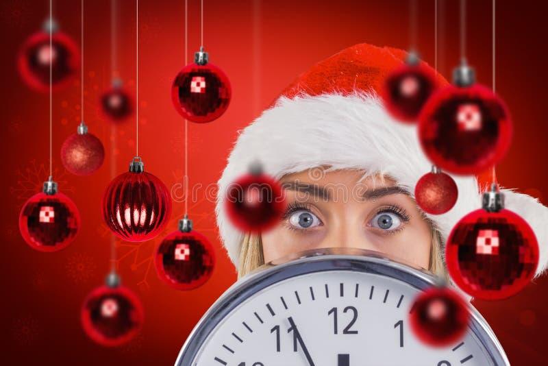 Σύνθετη εικόνα εορταστικού ξανθού παρουσιάζοντας ένα ρολόι στοκ εικόνα