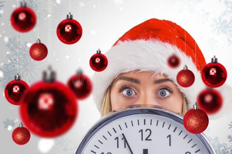 Σύνθετη εικόνα εορταστικού ξανθού παρουσιάζοντας ένα ρολόι στοκ εικόνες