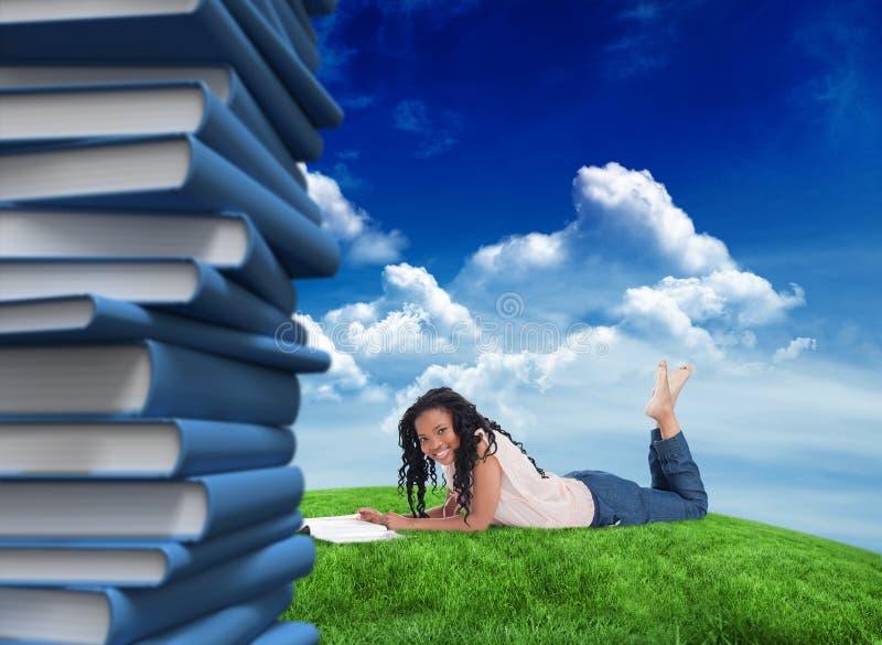 Σύνθετη εικόνα μιας γυναίκας που βρίσκεται στο πάτωμα που χαμογελά στη κάμερα με ένα περιοδικό μπροστά από την στοκ φωτογραφίες