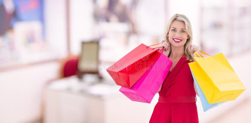 Σύνθετη εικόνα μοντέρνου ξανθού στις κόκκινες τσάντες αγορών εκμετάλλευσης φορεμάτων στοκ φωτογραφία με δικαίωμα ελεύθερης χρήσης