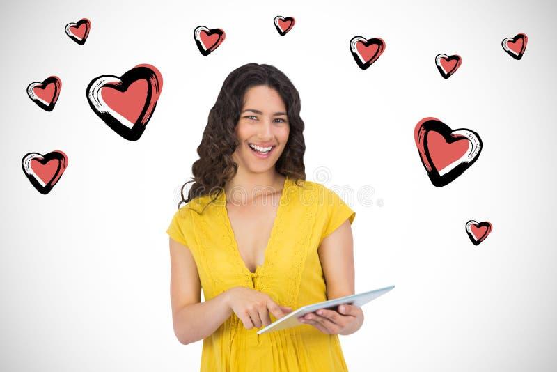 Σύνθετη εικόνα να τυλίξει γυναικών χαμόγελου περιστασιακό νέο στον υπολογιστή ταμπλετών της στοκ εικόνες με δικαίωμα ελεύθερης χρήσης