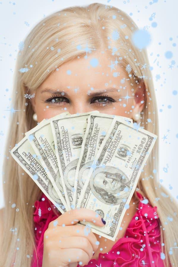 Σύνθετη εικόνα ξανθού κρύβοντας το πρόσωπό της με τα τραπεζογραμμάτια δολαρίων στοκ φωτογραφίες