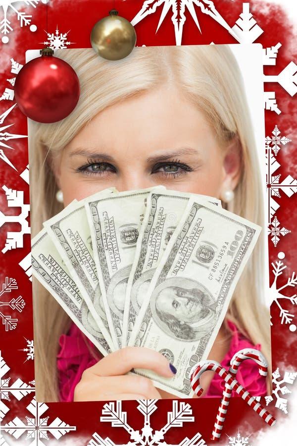 Σύνθετη εικόνα ξανθού κρύβοντας το πρόσωπό της με τα τραπεζογραμμάτια δολαρίων στοκ φωτογραφία με δικαίωμα ελεύθερης χρήσης