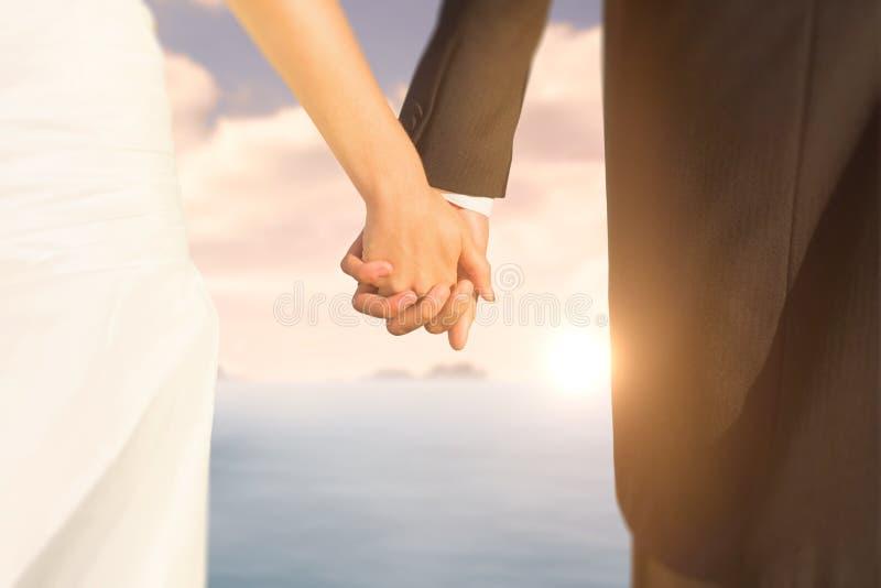 Σύνθετη εικόνα στενού επάνω των χαριτωμένων νέων newlyweds που κρατούν τα χέρια τους στοκ φωτογραφία με δικαίωμα ελεύθερης χρήσης