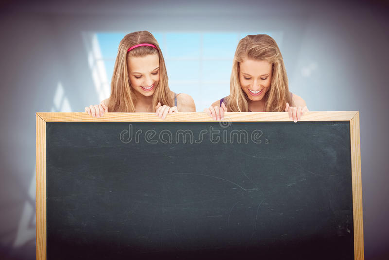 Σύνθετη εικόνα στενού επάνω δύο νέων γυναικών που κρατούν έναν κενό πίνακα στοκ εικόνες με δικαίωμα ελεύθερης χρήσης