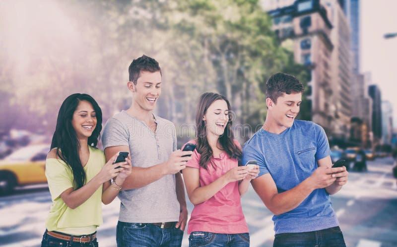 Σύνθετη εικόνα τεσσάρων γελώντας φίλων που στέλνουν τα κείμενα στα τηλέφωνά τους στοκ εικόνα
