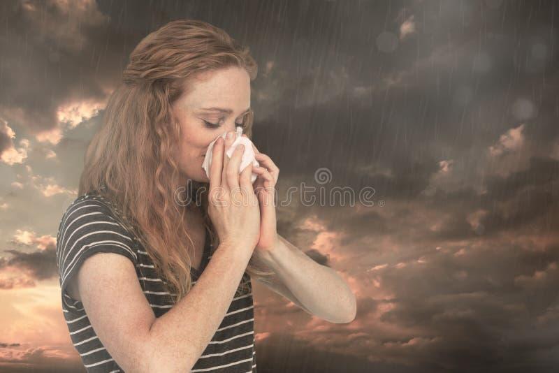 Σύνθετη εικόνα της άρρωστης ξανθής γυναίκας που φυσά τη μύτη της στοκ εικόνα