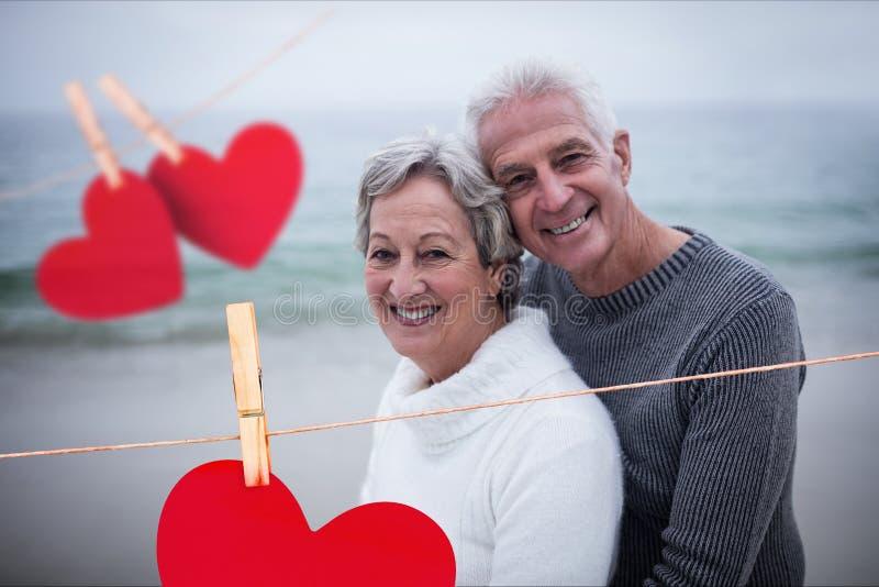 Σύνθετη εικόνα της ένωσης των καρδιών και του ανώτερου ζεύγους που αγκαλιάζουν στην παραλία στοκ φωτογραφία