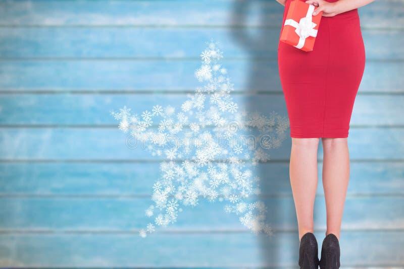 Σύνθετη εικόνα της αριστοκρατικής γυναίκας που κρατά ένα δώρο στοκ εικόνες