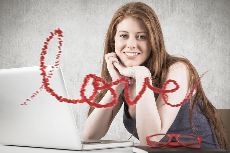 Σύνθετη εικόνα της αρκετά redhead εργασίας στο lap-top στοκ φωτογραφίες