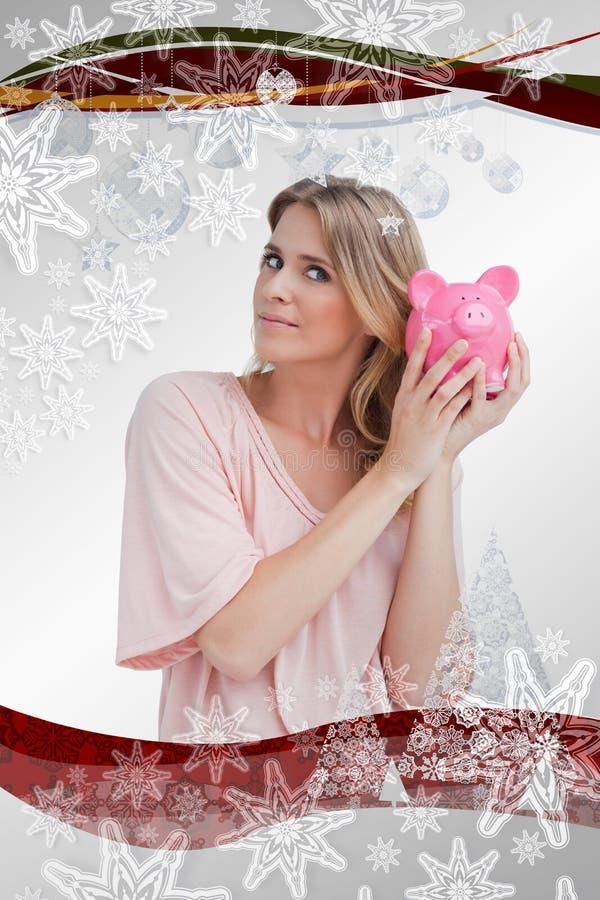 Σύνθετη εικόνα της γυναίκας που κρατά μια piggy τράπεζα μέχρι το κεφάλι της στοκ φωτογραφία