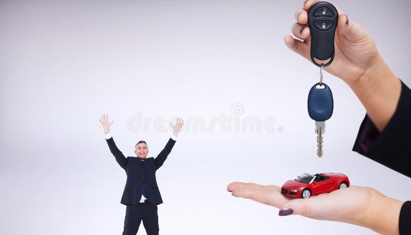 Σύνθετη εικόνα της γυναίκας που κρατά το βασικό και μικρό αυτοκίνητο στοκ εικόνα