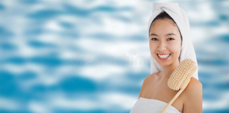 Σύνθετη εικόνα της γυναίκας που φορά μια πετσέτα για τη λήψη του λουτρού στοκ εικόνες με δικαίωμα ελεύθερης χρήσης